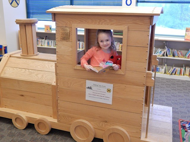 Young girl reading book on wooden train